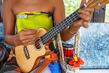 Beautiful local woman playing ukulele in Huahine island, Society Islands, French Polynesia, South Pacific.   Coastline and lagoon of Huahine island near Maroe bay, south Pacific ocean, OceaniaSouth Pacific.