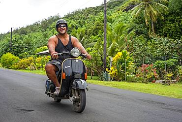 Portrait of a local fat man wirh motorbike in Huahine, Society Islands, French Polynesia, South Pacific.