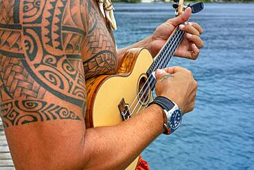 Local tattooed person playing the ukulele in Huahine, Society Islands, French Polynesia, South Pacific.