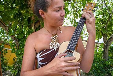 Beautiful local woman playing ukulele next to Bora Bora Vaitape dock, Society Islands, French Polynesia, South Pacific.