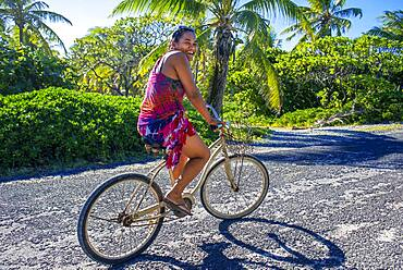 Local woman on a bicycle in the beach of Rangiroa, Tuamotu Islands, French Polynesia, South Pacific.