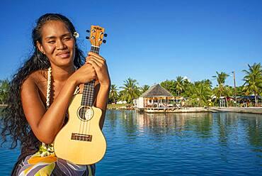 Beautiful local woman playing ukulele in Rangiroa beach, Tuamotu Islands, French Polynesia, South Pacific.