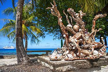 A sculpture with shells on a railing overlooking a tropical lagoon on the island of Fakarava in French Polynesia