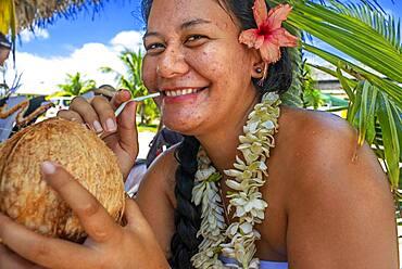Woman drinking coconut milk in Fakarava,  Tuamotus Archipelago French Polynesia, Tuamotu Islands, South Pacific.