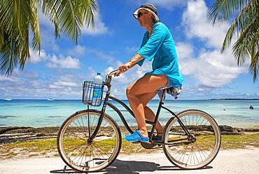 Tourist girl with a bike in Fakarava,  Tuamotus Archipelago French Polynesia, Tuamotu Islands, South Pacific.