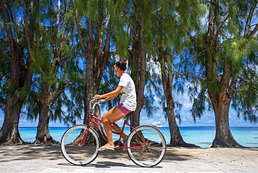 Local girl with a bike in Fakarava,  Tuamotus Archipelago French Polynesia, Tuamotu Islands, South Pacific.
