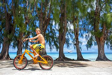 Tourist boy with a bike in Fakarava,  Tuamotus Archipelago French Polynesia, Tuamotu Islands, South Pacific.