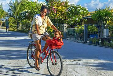 Local girl with a bike and small child in Fakarava,  Tuamotus Archipelago French Polynesia, Tuamotu Islands, South Pacific.