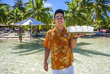 A waiter serves cocktails in Taha'a island resort, French Polynesia. Motu Mahana palm trees at the beach, Taha'a, Society Islands, French Polynesia, South Pacific.