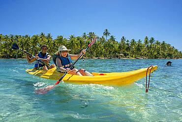 Kayaking in Taha'a island beach, French Polynesia. Motu Mahana palm trees at the beach, Taha'a, Society Islands, French Polynesia, South Pacific.