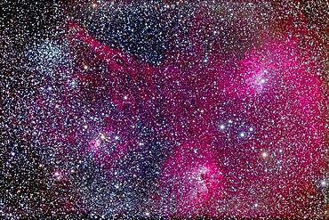 The complex area of clusters and nebulosity in central Auriga, including: M38 the Starfish Cluster and its smaller companion cluster NGC 1907; the emission/reflection nebulas NGC 1931, IC 417, IC 410 and IC 405 (from right to left here). Magenta and cyan (from emission and reflection components) IC 405 at right is the Flaming Star Nebula. Between IC 405 and IC 410 is the asterism known as The Little Fish.