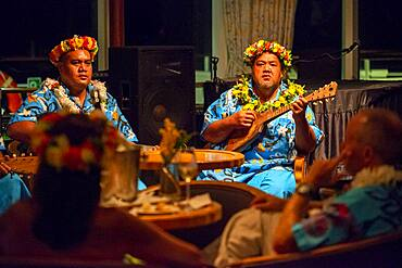 Entertainment group singing in the Paul Gauguin cruise ship. France, French Polynesia, Polynesian, South Pacific.