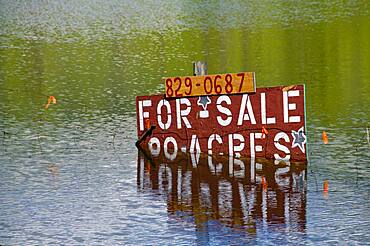 Flooded field property for sale sign.