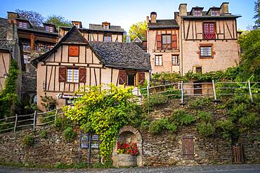 The small medieval village of Conques in France. It shows visitors its abbey-church and clustered houses topped by slate roofs.  Crossing of narrow streets and monolith to the fallen ones in the war in the old medieval village of Conques on coats of the river Dordou