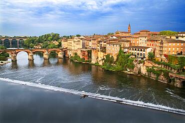 The Tarn River crossing Albi town. Pont Vieux bridge and the Church of Notre Dame du Breuil in Tarn village, Occitanie Midi Pyrenees France.