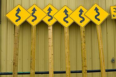 Roadside curve signs leaning on public works building.