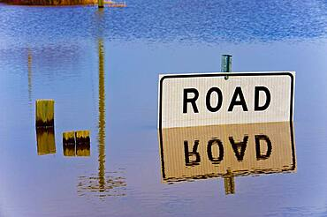 Road closed sign reflected in flood waters.
