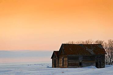 Old barns at prairie sunset in winter.