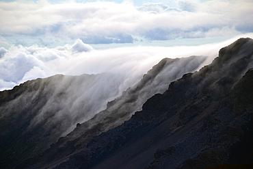 Clouds over a mountain edge at the summit of Haleakala volcano during sunrise, Maui, Hawaii, USA