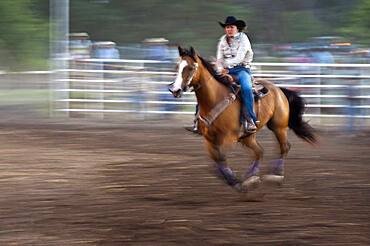 Horse and rider in rodeo barrel racing event.