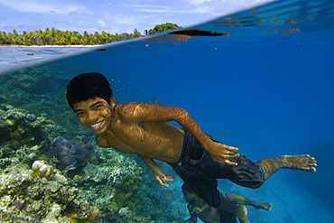 Over under image of marshallese boy smiling underwater next to coral reef and coconut trees lining the shore of Majikin Island, Namu atoll, Marshall Islands (N. Pacific).