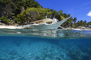 Over under of banca and sandy seafloor, Apo island Marine Reserve, Philippines.