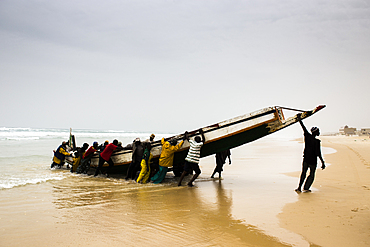 Men unload a fish canoe in the afternoon fish market in Mboro Plage beach when the canoes arrive loaded