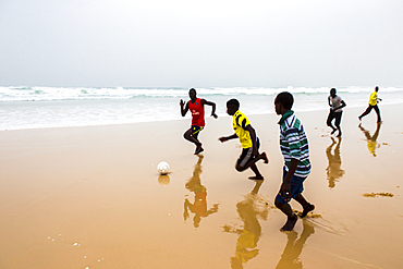 Boys playing football on the beach during the afternoon fish market in Mboro Plage beach when the canoes arrive loaded