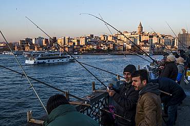 People fishing from Galata Bridge in front of Galata neighbourhood and Galata Tower during sunset in the Golden Horn