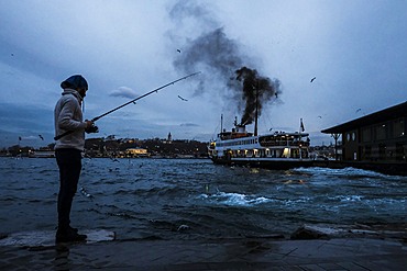 Man fishing in the Golden Horn in Galata neighbourhood while a ferry boat is sailing