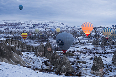 Cappadocia in winter covered with snow and hot-air balloon taking off near Göreme