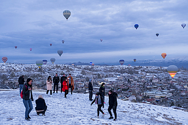 Cappadocia in winter covered with snow, tourists and hot-air balloon taking off near Göreme