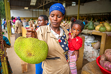 A woman holds her child under her arm while examining a jackfruit at outdoor market, Rwanda Farmers Market, in Rwanda