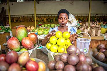 Woman reaches out for fruit in bins at outdoor market, Rwanda Farmers Market, in Rwanda in Rwanda