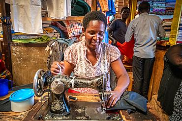 Seamstress working sewing machine, Kimironko Market, Kigali Rwanda