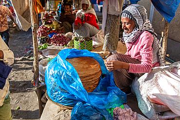 Woman smiling as she prepares Injera or Ethiopian flatbread at outdoor market, Deber Berhan, Ethiopia