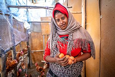 An Ethiopian farmer holding eggs from her chicken coop, Debre Berhan, Ethiopia.