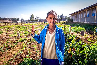A young Ethiopian farmer posing in a field for a photograph, Debre Berhan, Ethiopia