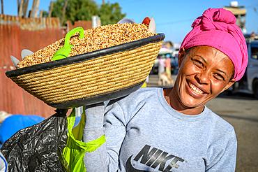 Smiling woman carrying basket full of Kolo or roasted barley on her shoulder, Debre Berhan, Ethiopia
