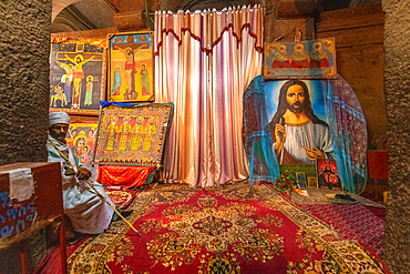 A man sits near a collection of Christian artwork within the church of Bet Medhane Alem (Church of the World Savior) in Lalibela, Ethiopia