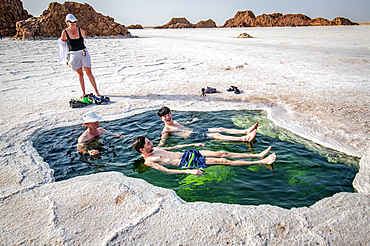 Tourists relax inside the water of Lake Karum, visible through a hole in the salt flat, Danakil Depression, Ethiopia.