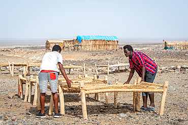 Two men set up cots in a salt miner camp in the Danakil Depression, Ethiopia