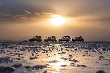 Tourist on the salt flats next to Land Cruisers in the Danakil Depression, Ethiopia