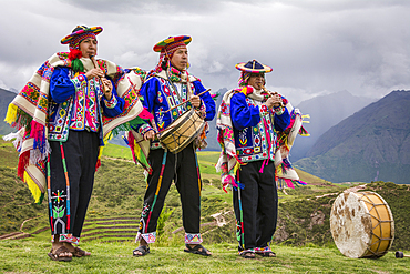 Quechua men in traditional clothing with musical instruments in performance at El Parador de Moray, Sacred Valley, Peru.