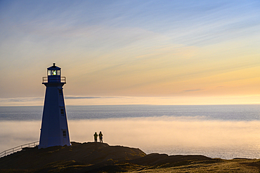 Visitors at Cape Spear Lighthouse with fog bank over the Atlantic Ocean; St. John's, Newfoundland, Canada.