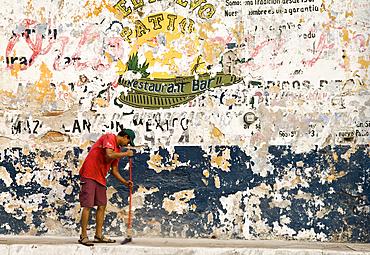 Man sweeping sidewalk and faded signs on wall, Avenida Zaragoza, old town Mazatlan, Mexico.