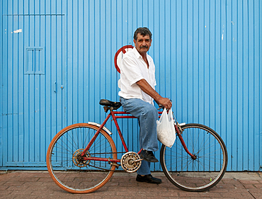 Man on bicycle in front of blue wall, Tonal·, Mexico.