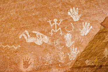 Native American pictographs, including Kokopeli and hand shapes, on sandstone walls of Chinle Wash; Canyon de Chelly National Monument, Arizona.