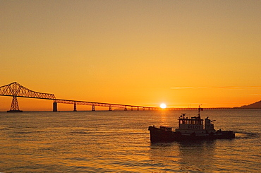 "Pilot Boat ""Arrow 2"" and the Astoria-Megler Bridge, connecting Oregon and Washington across the Columbia River, at sunset; Astoria, Oregon."