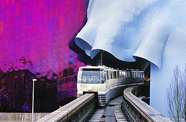 Monorail emerging from tunnel through Experience Music Project at Seattle Center; Seattle, Washington.